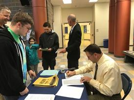 Principals of ERHS checking students into registration line